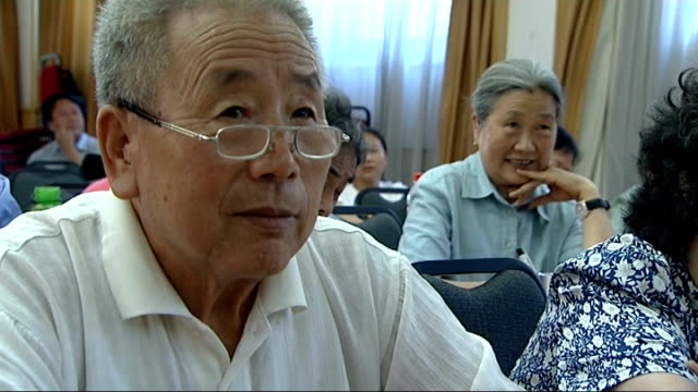 beijing olympic games 2008: residents learning polite english phrases; close shot elderly man speaking in class sot two students having conversation... - 2008年北京夏季オリンピック点の映像素材/bロール