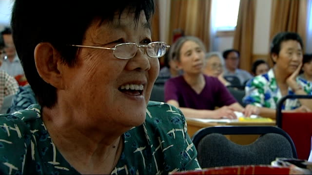 beijing olympic games 2008: residents learning polite english phrases; close shot elderly woman repeating english phrases telling the time sot more... - 2008年北京夏季オリンピック点の映像素材/bロール
