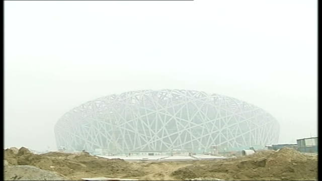 beijing olympic games: world's fastest marathon runner pulls out of games; china: beijing: birds nest olympic stadium seen through haze of smog... - bird's nest stock videos & royalty-free footage