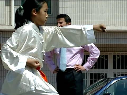 vídeos de stock, filmes e b-roll de beijing olympics: sebastian coe visits chinese stadium and school; ext children in playground practising martial arts / lord coe watching / lord coe... - sebastian coe
