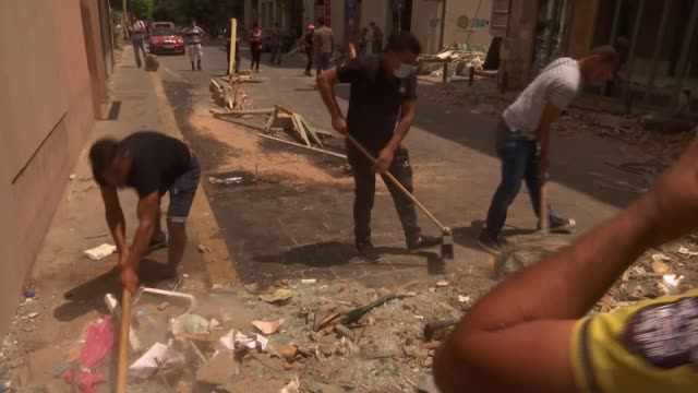 britain has promised another £20 million in urgent humanitarian aid for lebanon; lebanon: beirut: ext various shots of men sweeping up broken glass... - rubble stock-videos und b-roll-filmmaterial