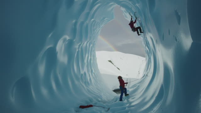 belayer assisting ice climber ascending glacier tunnel near rainbow / palmer, alaska, united states - höhle stock-videos und b-roll-filmmaterial