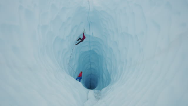 belayer assisting ice climber ascending glacier tunnel / palmer, alaska, united states - höhle stock-videos und b-roll-filmmaterial