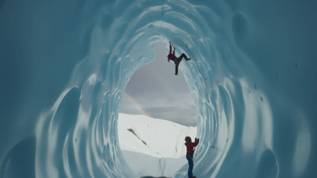 Belayer Assistingg ice climber ascending glacier tunnel near rainbow / Palmer, Alaska, United States