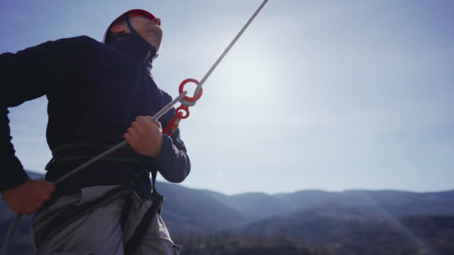 belayer controlling the rope that is attached to the climber - climbing rope stock videos & royalty-free footage