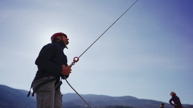 belayer controlling the rope that is attached to the climber - belaying stock videos & royalty-free footage