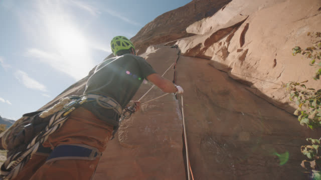 belayer looks up and feeds rope to lead climber high above on sandstone rock face. - rock face stock videos & royalty-free footage