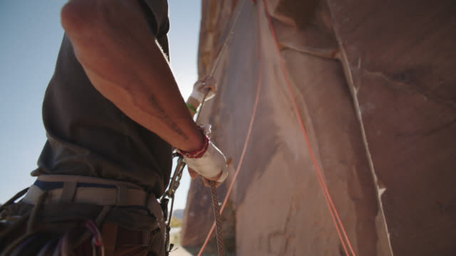 cu. belayer pulls rope to create slack for climber on rock face. - imbracatura di sicurezza video stock e b–roll
