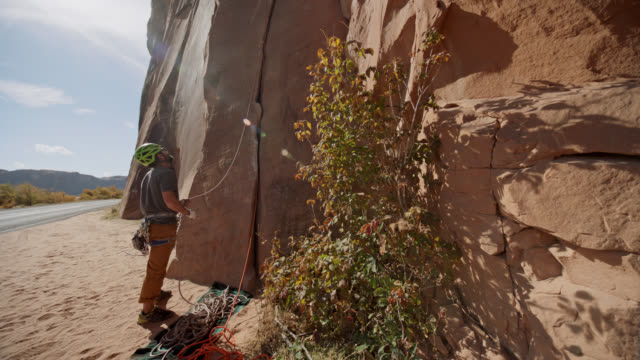 belayer stands at the base of majestic sandstone rock face and looks up at the climber high above. - sandstone stock videos & royalty-free footage
