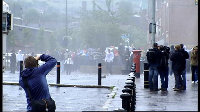 belfast ardoyne ext back view of row of riot police water cannon being fired at protesters orange order march along road with police escort - water cannon stock videos and b-roll footage