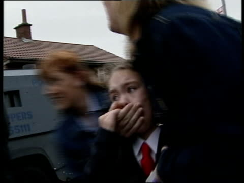 belfast: ardoyre ext young girl being comforted by mother as walking towards to catholic school past protestant protestors catholic parents towards... - belfast stock-videos und b-roll-filmmaterial