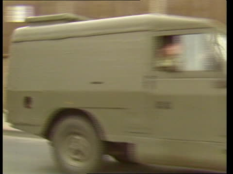 belfast: ext side army landrover l-r l-r as to bv down road int cms side armed ruc officer seated in back of landrover - b/g two soldiers seated in... - land rover stock videos & royalty-free footage