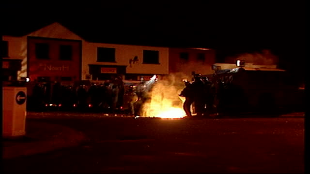 belfast: sectarian riots; northern ireland: belfast: ardoyne: ext bv catholic schoolgirl and mother away along street and stopped by riot police... - belfast stock-videos und b-roll-filmmaterial