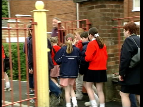 sectarian riots second night itn ireland belfast ardoyne ext ms group of catholic mothers towards along road as taking daughters to school track back... - アルスター州点の映像素材/bロール