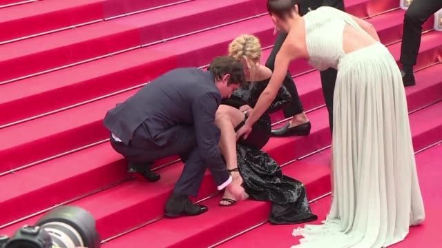 belgian actress virginie efira ends up sitting on cannes's famous red carpet steps as her shoe straps came repeatedly undone during the premiere... - 72nd international cannes film festival stock videos and b-roll footage