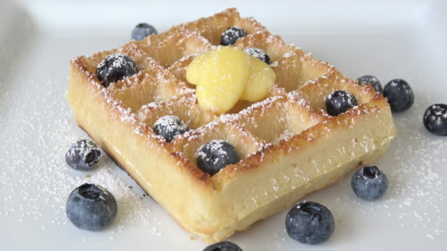 belgian waffles with maple syrup, blueberries, and powdered sugar - waffles stock videos and b-roll footage
