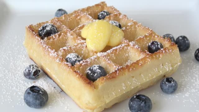 vídeos y material grabado en eventos de stock de waffles belgas con sirope de arce, arándanos y azúcar en polvo - waffles belgas