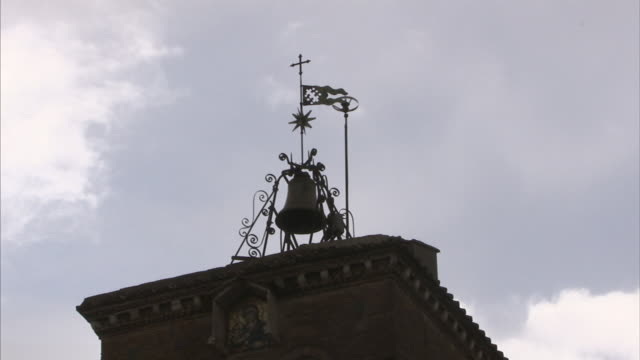 Bell and ornamental ironwork top the tower of Rome's Church of Santa Maria in Trastevere.
