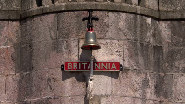"""a bell hangs above a sign with the name """"britannia"""" on it. available in hd. - dartmouth england stock videos & royalty-free footage"""
