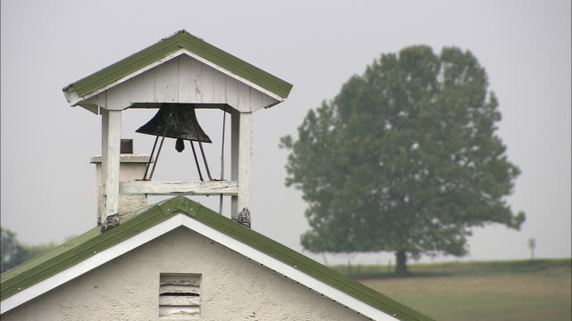 vidéos et rushes de a bell hangs from a copula on an amish school. - amish