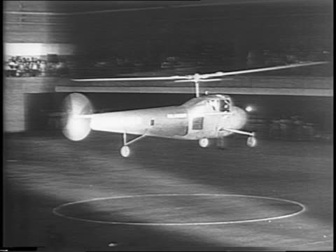 bell helicopter hovering in air / helicopter wheeled into buffalo 65th regiment armory national guard hangar / crowd of civil air patrol soldiers... - waffenlager stock-videos und b-roll-filmmaterial