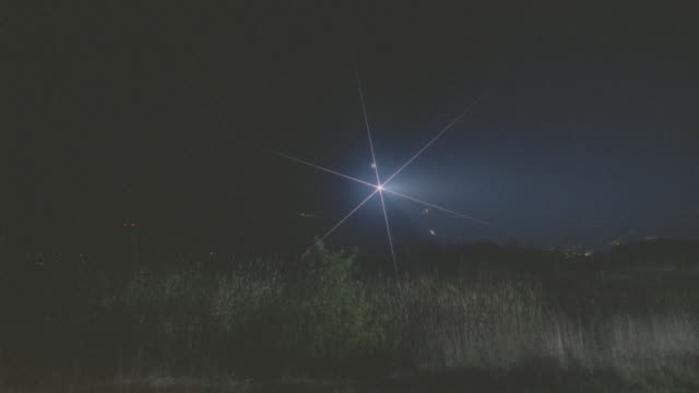 bell jet ranger helicopter lands in open field, then t/o; searchlight on (star filter) - night - helicopter stock videos & royalty-free footage