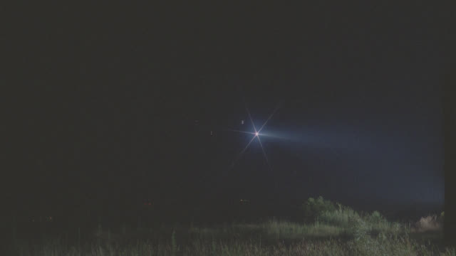 bell jet ranger helicopter to camera, lands in open field; searchlight on (star filter) - night - searchlight stock videos & royalty-free footage