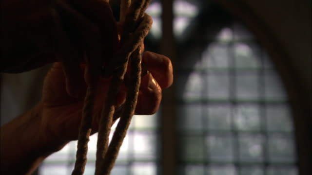 Bell ringer ties knot into rope in church, UK