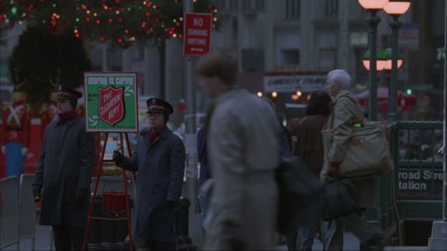bell ringers stand by a salvation army bucket as pedestrians pass by. - salvation army stock videos & royalty-free footage