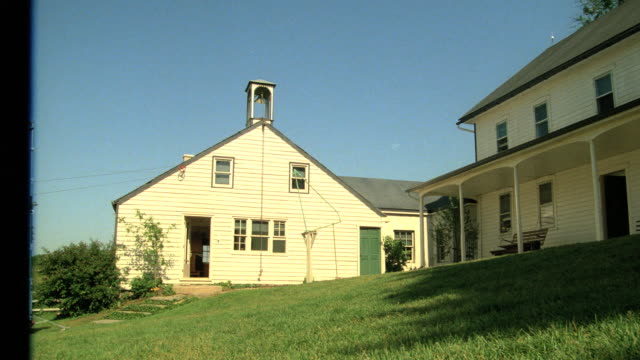 a bell tower accents the top of a white building on an amish farm. - アーミッシュ点の映像素材/bロール