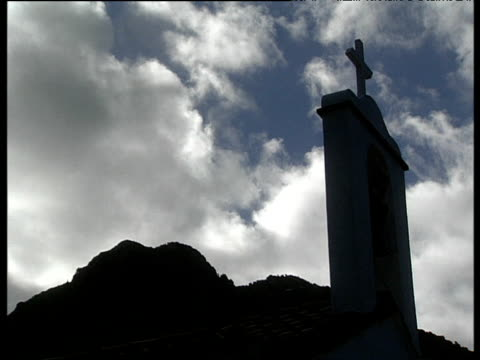 bell tower and cross on top of church with mountains in background silhouetted against bright sky. tenerife - 大西洋諸島点の映像素材/bロール