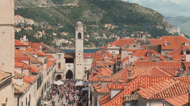 HA WS ZO Bell tower and people walking in the Stradun with the Adriatic in the background/ Dubrovnik, Dalmatia