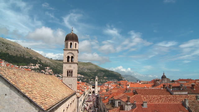 HA WS Bell tower at Franciscan church, clouds, and rooftops/ TD WS crowd walking around the Stradun/ Dubrovnik, Dalmatia