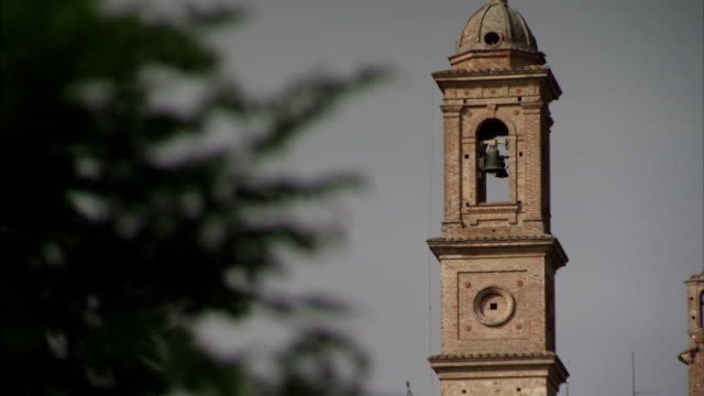 a bell tower characterizes a brick building in the tuscan countryside. available in hd. - bell tower tower stock videos and b-roll footage