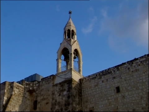 a bell tower rises above a stone wall on the church of the nativity in bethlehem. - church of the nativity stock videos and b-roll footage