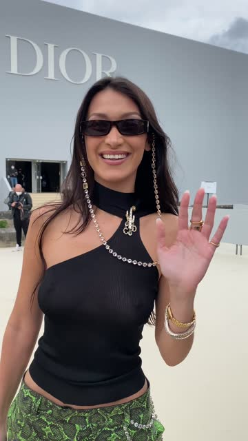 bella hadid wears sunglasses with a bejeweled / diamonds chain, a black off-shoulder cropped top with turtleneck, green leather snake print pattern... - long hair stock videos & royalty-free footage