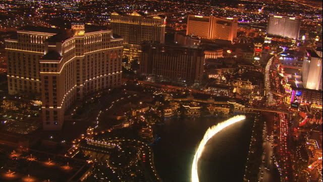 ws bellagio hotel casino with lighted dancing waters of synchronized water fountain rising upward moving across las vegas boulevard behind paris... - palace stock-videos und b-roll-filmmaterial