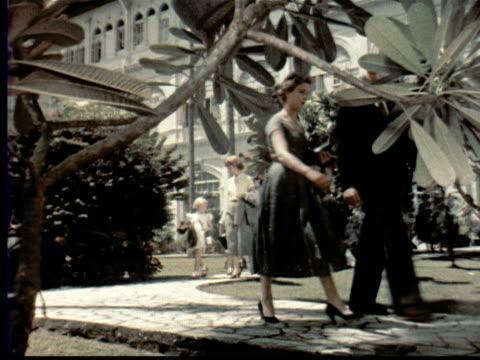 vídeos y material grabado en eventos de stock de 1957 montage bellboy carries suitcases has travelers walk through gardens of raffles hotel to their rooms. bellboy + couple enters room. woman opens blinds + looks out window / singapore / audio - 1957