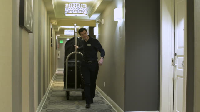 Bellhop pulling a luggage cart into a room