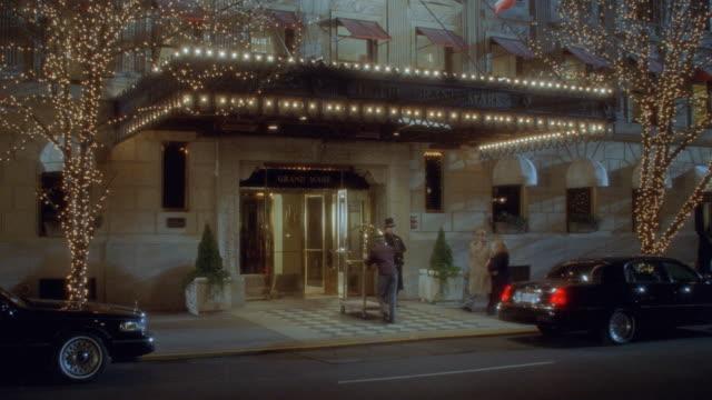 vídeos y material grabado en eventos de stock de a bellhop pushes a luggage cart through the entrance to the hotel grand mark in new york. - hospitalidad