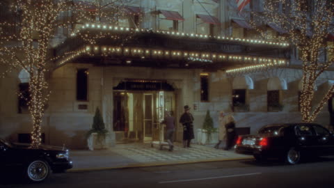 vidéos et rushes de a bellhop pushes a luggage cart through the entrance to the hotel grand mark in new york. - palace