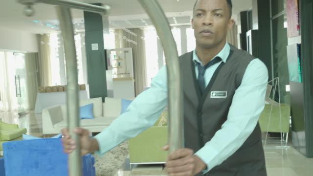 vídeos y material grabado en eventos de stock de bellhop putting suitcases on luggage cart in hotel lobby - three quarter length