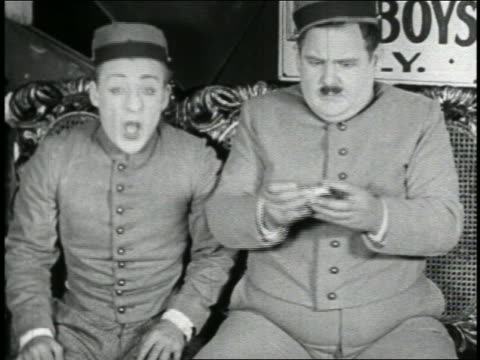 b/w 1923 bellhop sneezing as other rolls cigarette / short - b rolle stock-videos und b-roll-filmmaterial