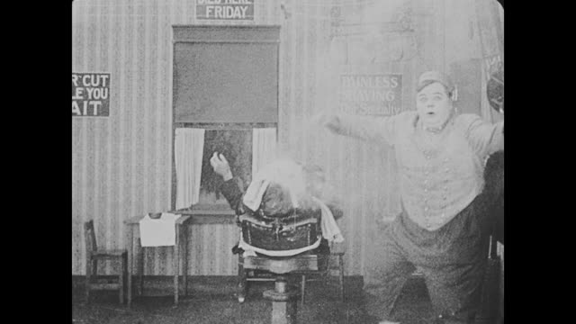 1918 Bellhop (Fatty Arbuckle) takes a steaming towel off of an uncomfortable barbershop customer's face and then applies aftershave to the customer's face