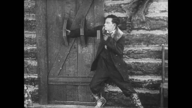 1922 Belligerent man (Buster Keaton) enters woman's cabin before startled by approaching man