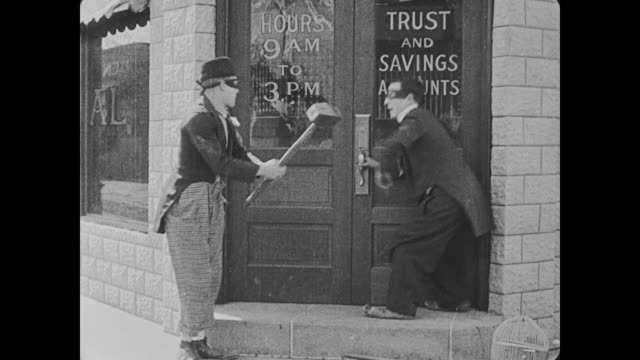 1918 bellman (buster keaton) and his supervisor break into the bank after a group of men have done the same, a fight ensues between them, and man (buster keaton) attempts to escape by jumping over office partitions and through windows - thief stock videos & royalty-free footage