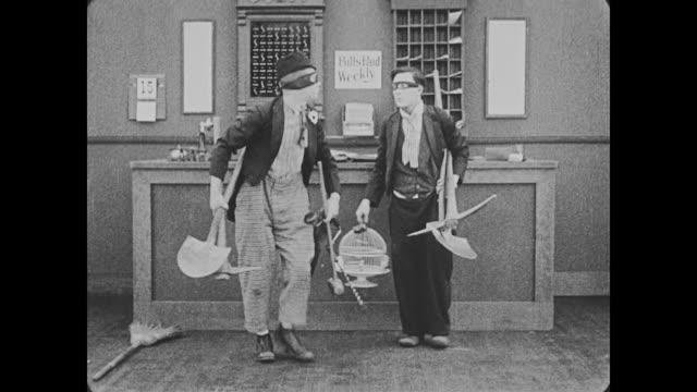 1918 bellman (buster keaton) and his supervisor, wearing burglar masks take shovels and picks from behind hotel reception desk - burglar stock videos & royalty-free footage