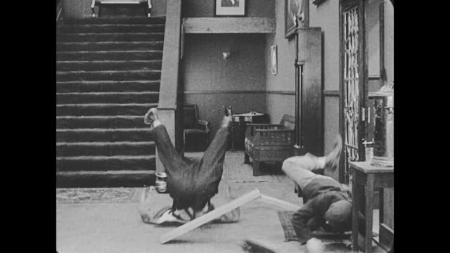 vidéos et rushes de 1918 bellman (buster keaton) bounces on a lodged piece of wood in the hotel lobby holding a telephone, the hotel receptionist takes the phone from him and cuts the wood with a saw, finally stopping man from bouncing and causing him to fall to the floor - 1918