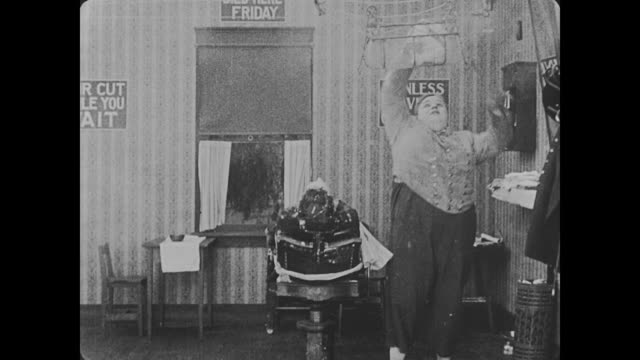 1918 bellman (fatty arbuckle) sends a towel, via a pulley system, from the barbershop to the kitchen, where it is stacked in hot water then sent back to bellman so he can place it on his customer's face - fatty arbuckle stock videos and b-roll footage