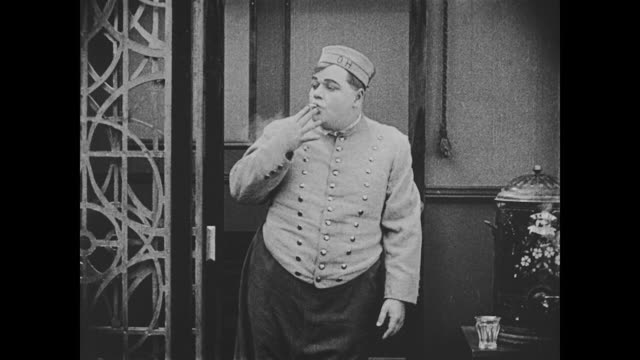 1918 Bellman (Fatty Arbuckle) smokes a lit cigarette that was hidden in his mouth and nervously disposes of it in a nearby canister when a hotel receptionist who assists a couple furiously rings a bell